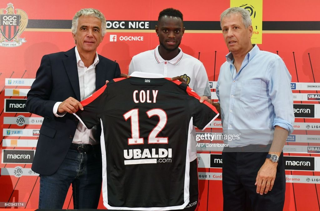 OGC Nice football club's new recruit Senegalese defender Racine Coly poses with his new jersey between Swiss head coach Lucien Favre (R) and French President Jean-Pierre Rivere (L) during a press conference to present the club's new players on September 4, 2017 at the Allianz Riviera stadium in Nice, southeastern France. /