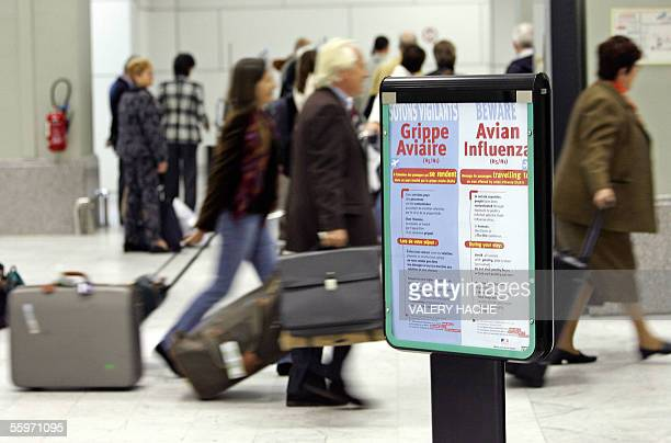 Passengers arriving from Istanbul walk by a sign informing about the bird flu in the terminal A of the Nice Cote D'Azur Airport 20 October 2005 The...