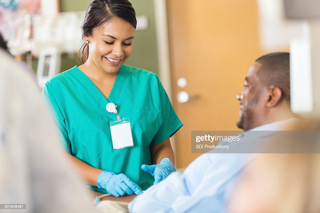 Nice hospital phlebotomist taking a sample from a patient : Stock Photo