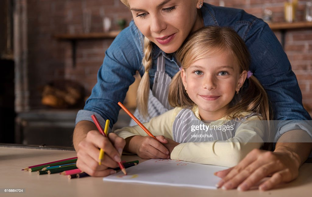 Nice little girl drawing with her mother in the kitchen : Stock Photo
