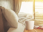 Cup of coffee and red glasses on wooden table in the morning bedroom.Vintage style