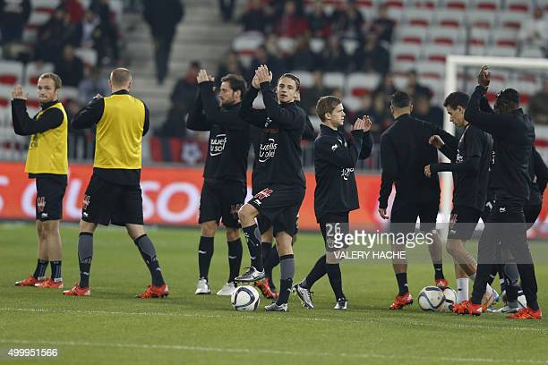 Nice players applaud as they warm up prior to the French L1 football match Nice vs Paris SaintGermain on December 4 2015 at the 'Allianz Riviera'...