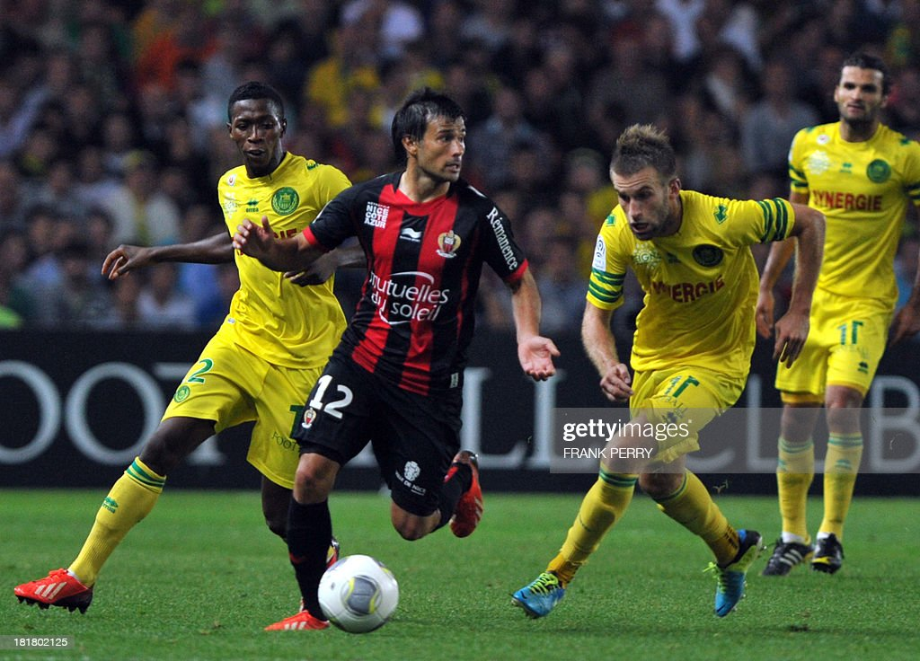 Nice's Argentinian forward Dario Cvitanich (C) vies with Nantes' French midfielder Lucas Deaux (R) during a French L1 football match Nantes against Nice on September 25, 2013 in La Beaujoire stadium in Nantes, western France.