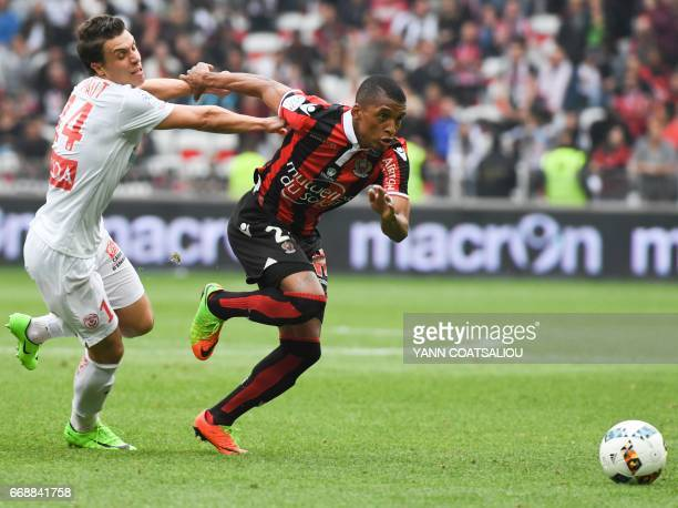 Nice's Brazilian defender Dalbert Henrique runs with the ball as Nancy's French defender Joffrey Cuffaut attempts to block him during the French L1...