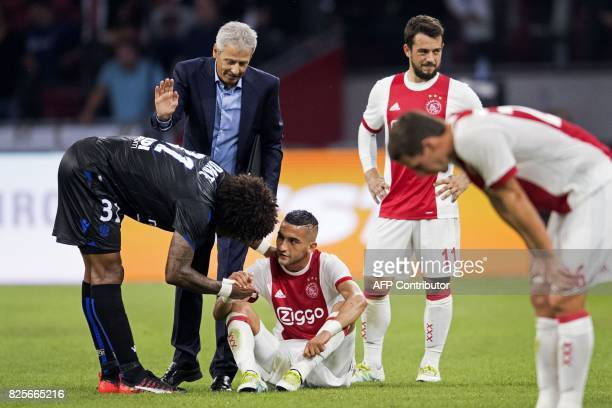Nice's captain and defender Bonfim Costa Dante comforts Ajax's midfielder Hakim Ziyech after Ajax were knocked out of the Champions League second leg...