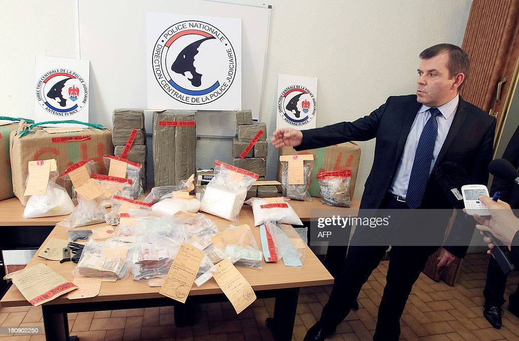 Nice's Divisional Police Commissioner Philippe Frizon presents 4kg of Cocaine, one of heroin and 250kg of cannabis seized during the dismantling of a drug traffic after an inquiry by the Inter region police direction (DIPJ) of Marseille, on September 17, 2013 in Nice. AFP PHOTO / JEAN CHRISTOPHE MAGNENET