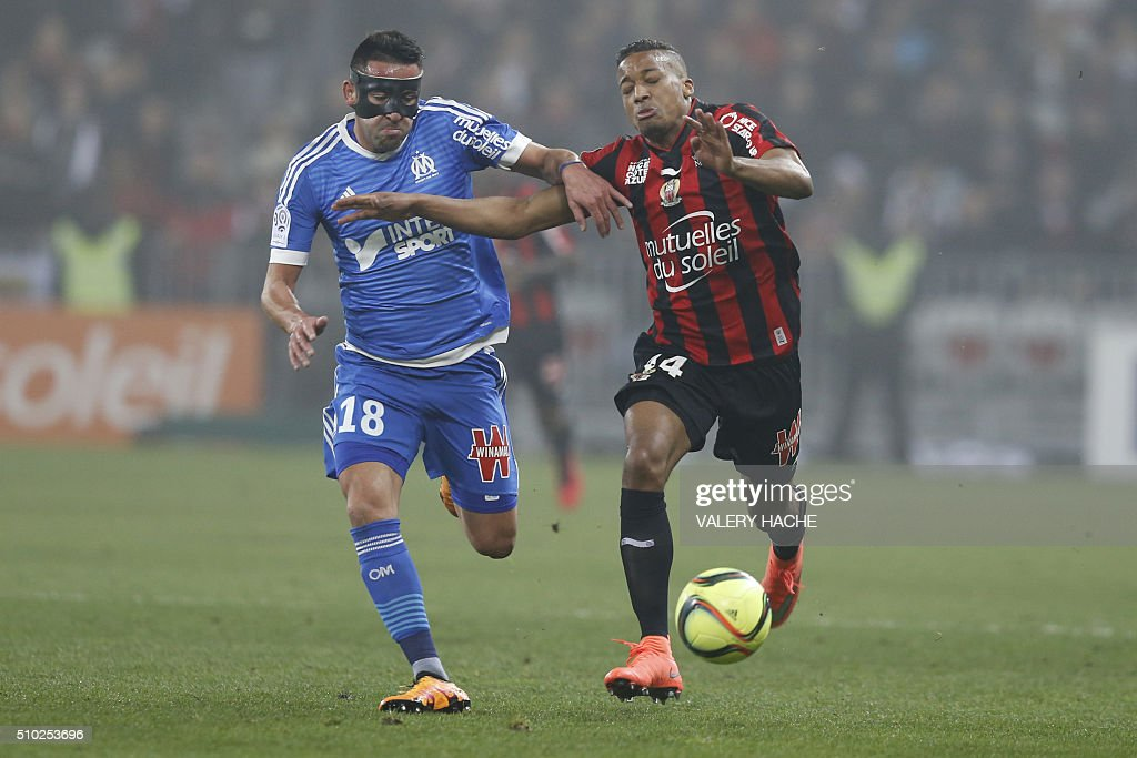 Nice's French forward Alassane Plea (R) vies with Marseille's Chilian midfielder Mauricio Anibal Isla (L) during the French L1 football match Nice (OGC Nice) vs Marseille (OM) on February 14, 2016 at the 'Allianz Riviera' stadium in Nice, southeastern France. AFP PHOTO / VALERY HACHE / AFP / VALERY HACHE