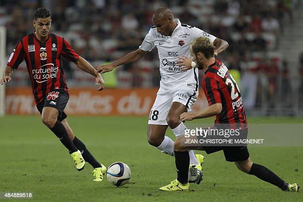 Nice's French forward Hatem Ben Arfa and Nice's French forward Valere Germain vies with Caen's Beninese midfielder Jordan Adeoti during the French L1...