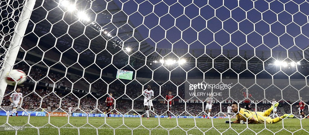 Nice's French goalkeeper Yoan Cardinale looks at the ball kicked by Lille's French defender Franck Beria as it enters his goal during the French L1...