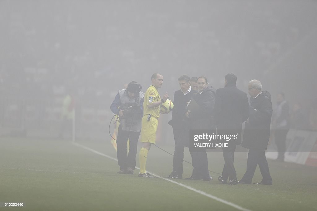 Nice's French head coach Claude Puel (C) speak with the referee as the match is interrupted due to smoke bombs during the French L1 football match Nice (OGC Nice) vs Marseille (OM) on February 14, 2016 at the 'Allianz Riviera' stadium in Nice, southeastern France. AFP PHOTO / VALERY HACHE / AFP / VALERY HACHE