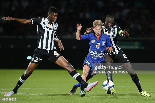 Nice's French midfielder Vincent Koziello vies with Angers' Congolese forward Ferebory Dore and Angers' Senegalese midfielder Cheikh N'Doye during...