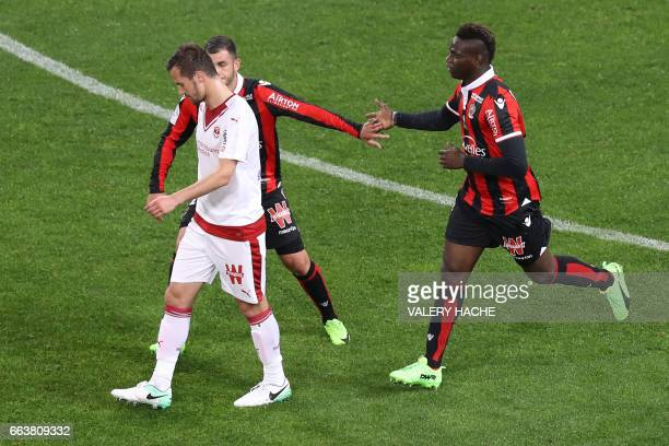 Nice's Italian forward Mario Balotelli is congratulated by teammates after scoring a goal during the French L1 football match Nice vs Bordeaux on...