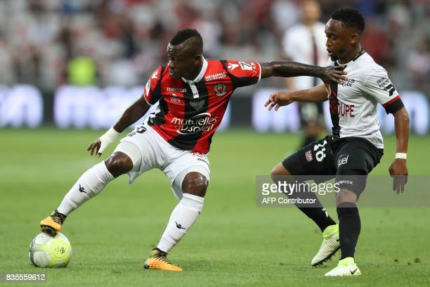 Nice's Ivorian midfielder Jean Michael Seri vies with Guingamp's SouthAfrican midfielder Lebogang Phiri during the French L1 football match Nice vs...