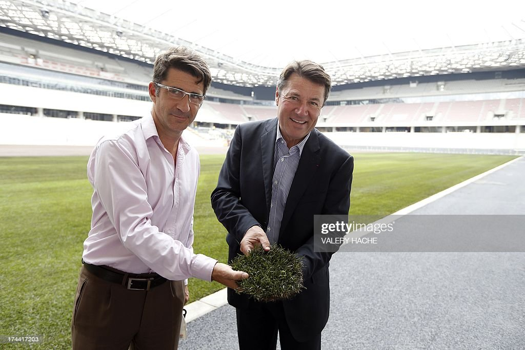 Nice's mayor Christian Estrosi (R) and Nice's Eco Stadium President Xavier Lortat-Jacob (L) poses with a clump of grass in front of the new field of the Allianz Riviera, Nice's new stadium, in Nice, southeastern France on July 25, 2013. The stadium is planned to be used for the UEFA Euro 2016 event and French L1 football matches and events such as the Games of la Francophonie.