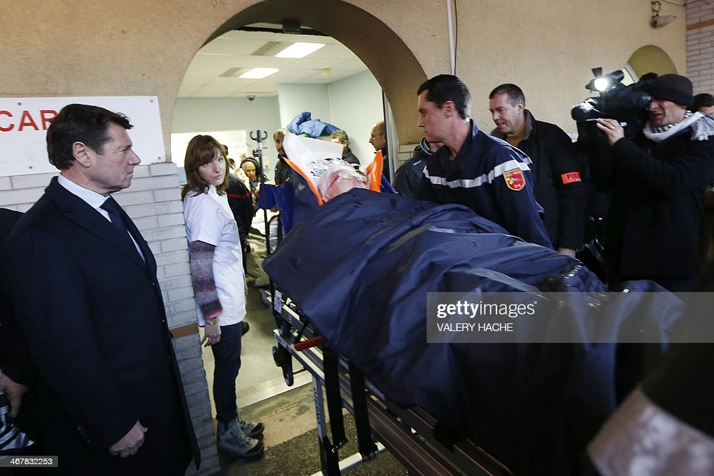 Nice's mayor Christian Estrosi (L) watches an injured person, laying on a stretcher, arriving at the hospital of Nice, southern France, after a train derailed near Digne-les-Bains in the French Alps on February 8, 2014. Two women were killed when a massive falling boulder hit a passing train in the French Alps on Saturday, leaving one of its carriages dangling precariously off a steep, snow-covered embankment. Eight people were injured in the accident which took place as the train travelled from the coastal city of Nice to the popular tourist town of Digne-les-Bains along a narrow, winding, and sometimes breathtakingly steep track.