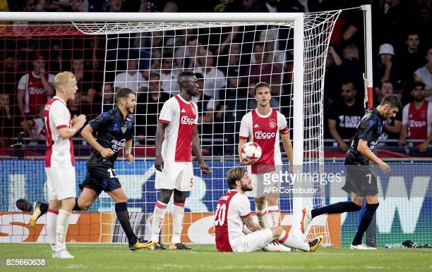 Nice's midfielders LeesMelou and Valentin Eysseric are watched by Ajax players as they celebrate after their unseen teammate Vincent Marcel scored...