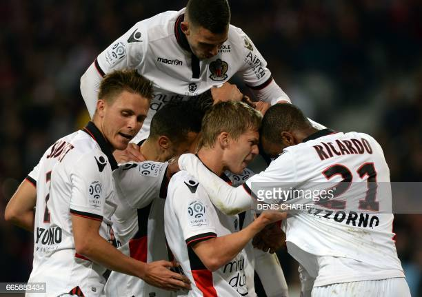 Nice's players celebrate with their Italian forward Mario Balotelli after he scored a goal during the French L1 football match between Lille and Nice...