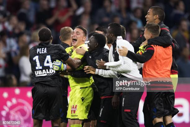 Nice's players led by goalkeeper Yoan Cardinale and forward Alassane Plea celebrate after they qualified for the Champions League following their 22...