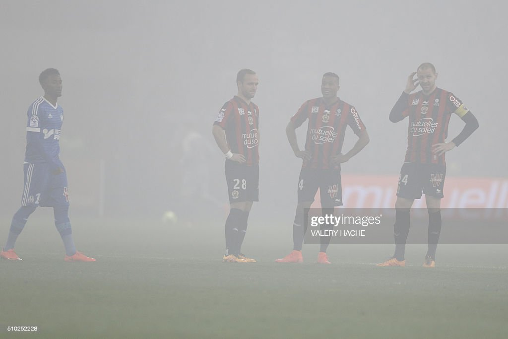 Nice's players wait as the match is interrupted due to smoke bombs during the French L1 football match Nice (OGC Nice) vs Marseille (OM) on February 14, 2016 at the 'Allianz Riviera' stadium in Nice, southeastern France. AFP PHOTO / VALERY HACHE / AFP / VALERY HACHE