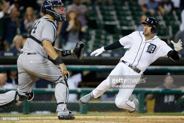 Nicholas Castellanos of the Detroit Tigers slides into home plate to score against catcher Gary Sanchez of the New York Yankees on an insidethepark...