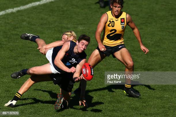Nicholas Coffield of Vic Metro gets his handball away while being tackled by Jonathan Frampton of Western Australia during the U18 Championships...