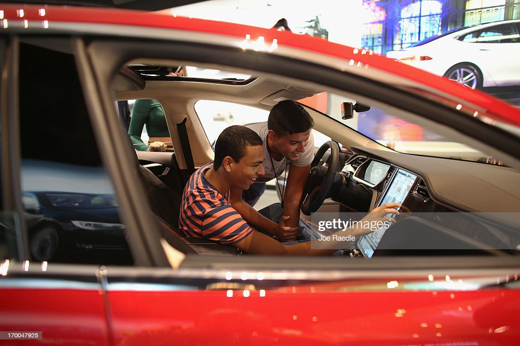 Nicholas Craan (L) and Francesco Campoy look at a Tesla motor company car in a dealership at the Dadeland Mall on June 6, 2013 in Miami, Florida. The electric car maker is trying to make a move by selling their cars, that can cost between $62,400 and $82,400, into malls and stores.