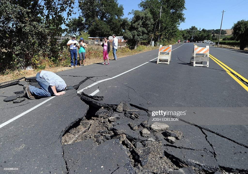 Nicholas George looks under a buckled highway just outside of Napa, California after earthquake struck the area in the early hours of August 24, 2014. California's governor Jerry Brown declared a state of emergency Sunday following a strong 6.0-magnitude earthquake that seriously injured three people including a child and ignited fires in the scenic Napa valley wine region. The US Geological Service said that the quake was the most powerful to hit the San Francisco Bay area since the 1989 6.9-magnitude Loma Prieta earthquake.