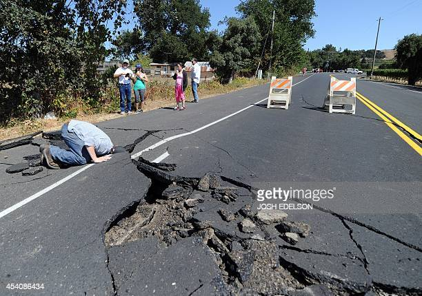Nicholas George looks under a buckled highway just outside of Napa California after earthquake struck the area in the early hours of August 24 2014...