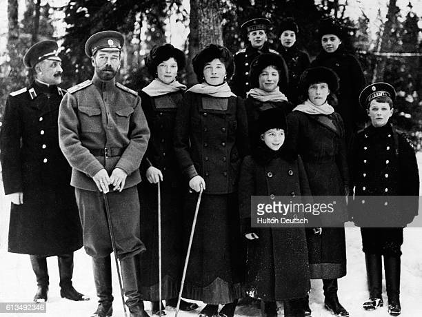 Nicholas II the last Czar of Russia stands outdoors at Tsarskoye Selo with his children and nephews near or just after the time of his abdication in...