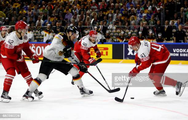 Nicholas Jensen of Denmark challenges Philip Gogulla of Germany for the puck during the 2017 IIHF Ice Hockey World Championship game between Denmark...