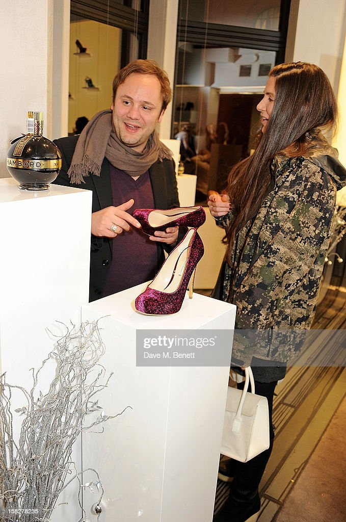 Nicholas Kirkwood (L) and Elizabeth Saltzman Walker attend a Christmas drinks hosted by designer Nicholas Kirkwood to celebrate his partnership with Chambord black raspberry liquer, and launch the limited edition shoe 'The Chambord' at the Nicholas Kirkwood Mount Street store on December 12, 2012 in London, England.
