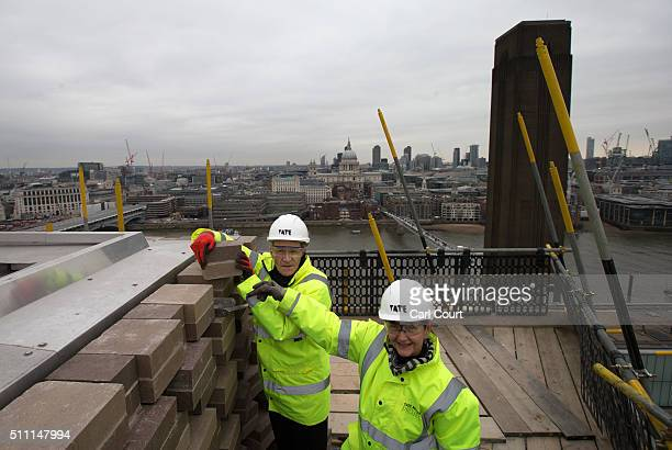 Nicholas Serota director of the Tate art museums and galleries and Frances Morris director of the Tate Modern lay the last brick in the extension of...