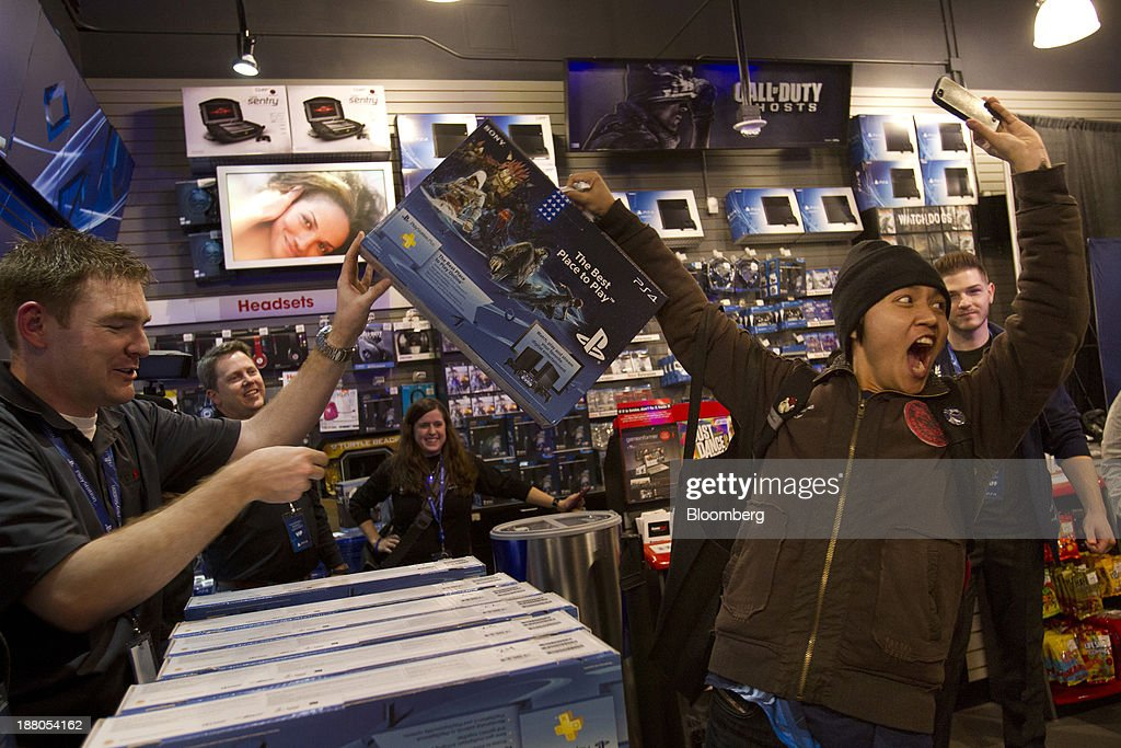 Nicholas Swe, right, reacts after purchasing the Sony PlayStation 4 console during its midnight launch event in San Francisco, California, U.S., on Thursday, Nov. 14, 2013. Sony Corp., poised to release the PlayStation 4 game console this week, is confident it can meet analysts' sales estimates of 3 million units by year-end, exploiting an early advantage over Microsoft Corp.'s Xbox One. Photographer: Erin Lubin/Bloomberg via Getty Images