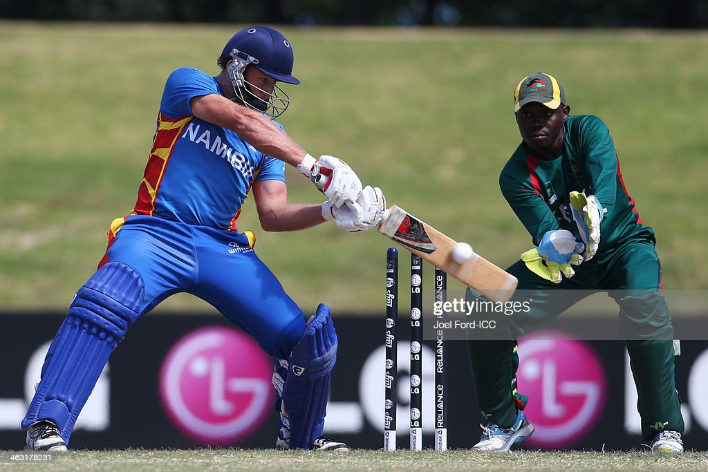 Nicholass Scholtz of Namibia plays a shot as wicketkeeper Morris Ouma of Namibia looks on during an ICC World Cup qualifying match between Namibia and Kenya on January 17, 2014 in Mount Maunganui, New Zealand.