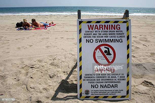 Nichole Canori and Patrick Woodard sunbathe near a sign that warns beachgoers to stay out of the water which is polluted by runoff from a nearby...