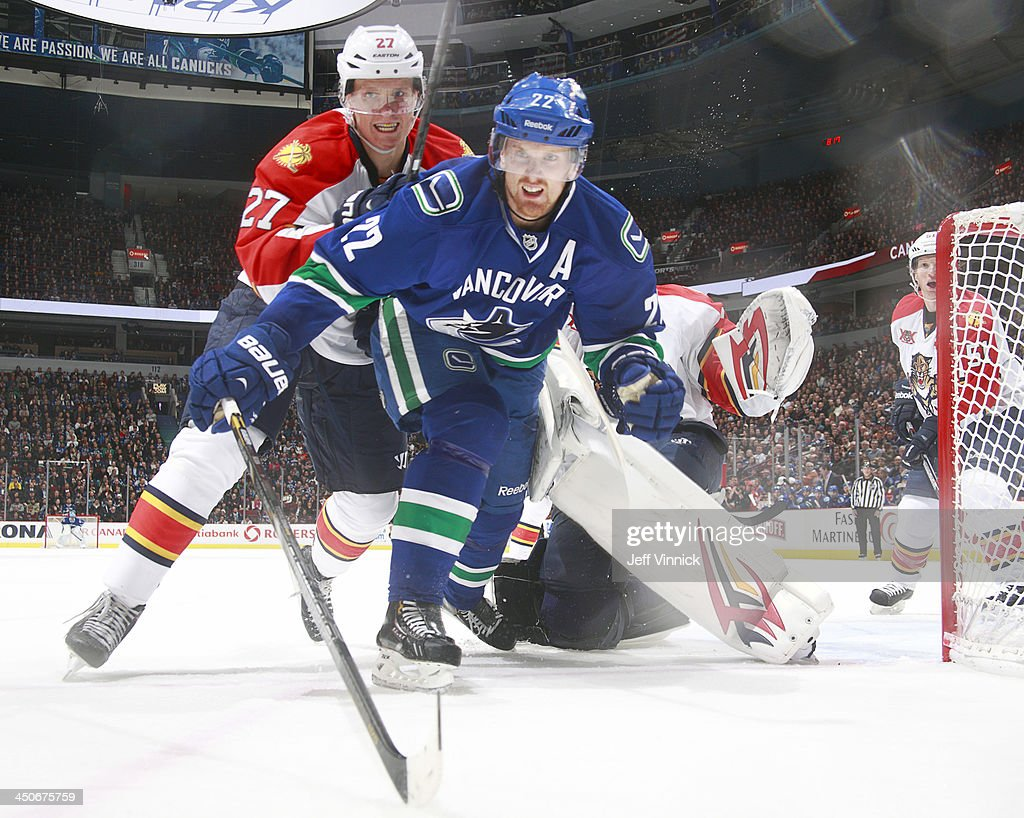 Nick Bjugstad #27 of the Florida Panthers checks Daniel Sedin #22 of the Vancouver Canucks during their NHL game at Rogers Arena on November 19, 2013 in Vancouver, British Columbia, Canada.