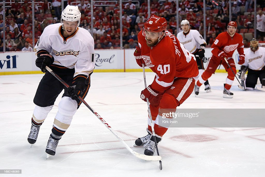 Nick Bonino #13 of the Anaheim Ducks and Henrik Zetterberg #40 of the Detroit Red Wings chase after a loose puck during Game Three of the Western Conference Quarterfinals during the 2013 NHL Stanley Cup Playoffs on May 4, 2013 at Joe Lewis Arena in Detroit, Michigan.