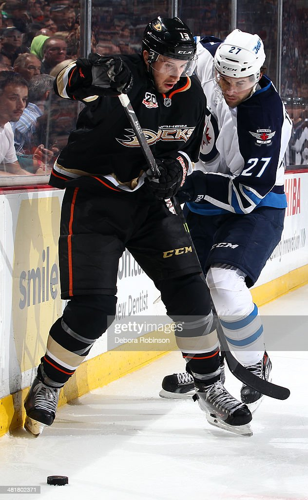 Nick Bonino #13 of the Anaheim Ducks battles for the puck against Eric Tangradi #27 of the Winnipeg Jets on March 31, 2014 at Honda Center in Anaheim, California.