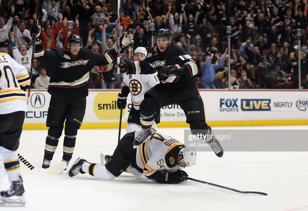 <a gi-track='captionPersonalityLinkClicked' href=/galleries/search?phrase=Nick+Bonino&family=editorial&specificpeople=5805660 ng-click='$event.stopPropagation()'>Nick Bonino</a> #13 of the Anaheim Ducks leaps over <a gi-track='captionPersonalityLinkClicked' href=/galleries/search?phrase=Adam+McQuaid&family=editorial&specificpeople=2238883 ng-click='$event.stopPropagation()'>Adam McQuaid</a> #54 of the Boston Bruins after scoring a goal, as <a gi-track='captionPersonalityLinkClicked' href=/galleries/search?phrase=Corey+Perry&family=editorial&specificpeople=213864 ng-click='$event.stopPropagation()'>Corey Perry</a> (L) #10 of the Ducks celebrates in the third period at Honda Center on January 7, 2014 in Anaheim, California. The Ducks defeated the Bruins 5-2.