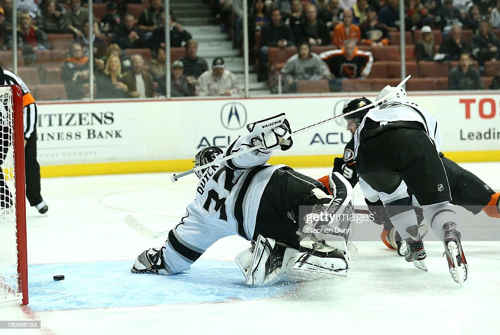 Nick Bonino #13 of the Anaheim Ducks scores the Ducks' first goal past goalie Jonathan Quick #32 and Jake Muzzin #6 of the Los Angeles Kings at Honda Center on February 2, 2013 in Anaheim, California.