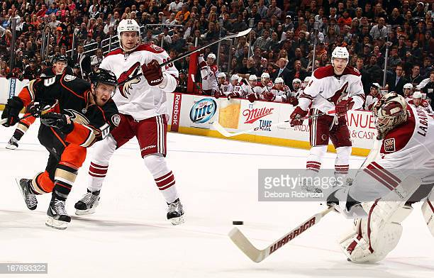Nick Bonino of the Anaheim Ducks shoots and Jason LaBarbera of the Phoenix Coyotes attempts to stop the puck with his stick during the game on April...