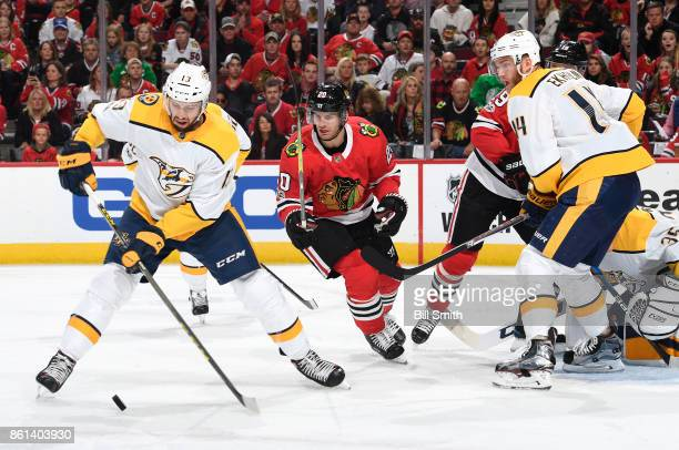 Nick Bonino of the Nashville Predators approaches the puck as Brandon Saad of the Chicago Blackhawks and Mattias Ekholm watch from the side in the...
