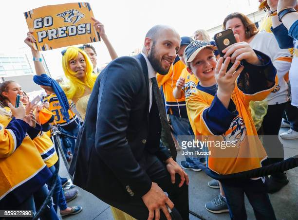 Nick Bonino of the Nashville Predators poses for photo with a young fan as he arrives for the home opener against the Philadelphia Flyers prior to an...