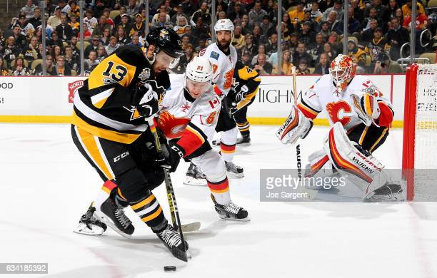 Nick Bonino of the Pittsburgh Penguins battles for the puck against Brett Kulak of the Calgary Flames at PPG Paints Arena on February 7 2017 in...