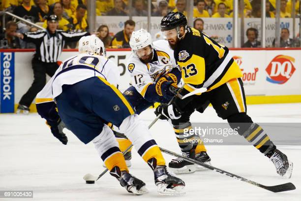 Nick Bonino of the Pittsburgh Penguins controls the puck against Mike Fisher and Roman Josi of the Nashville Predators during the first period in...