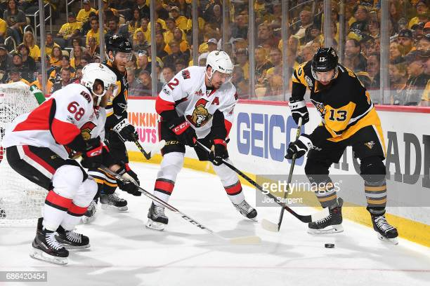 Nick Bonino of the Pittsburgh Penguins handles the puck against Dion Phaneuf of the Ottawa Senators in Game Five of the Eastern Conference Final...