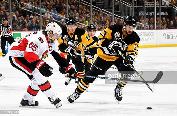 Nick Bonino of the Pittsburgh Penguins handles the puck in front of Erik Karlsson of the Ottawa Senators at PPG Paints Arena on December 5 2016 in...