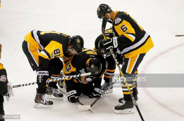 Nick Bonino of the Pittsburgh Penguins is helped off the ice after taking a shot in the food in the first period against the Nashville Predators in...