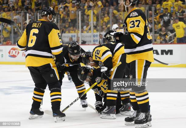 Nick Bonino of the Pittsburgh Penguins is helped off the ice by teammates after blocking a shot during the first period of Game Two of the 2017 NHL...