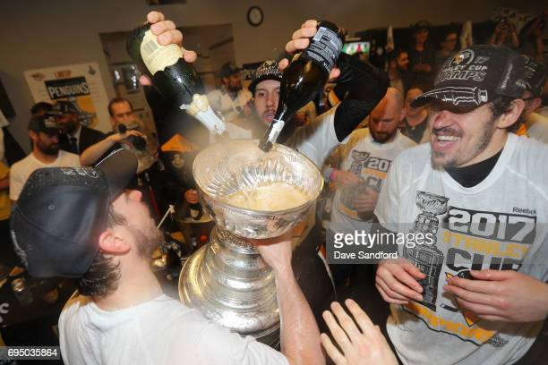Nick Bonino of the Pittsburgh Penguins pours champagne into the Stanley Cup in the locker room after Game Six of the 2017 NHL Stanley Cup Final at...